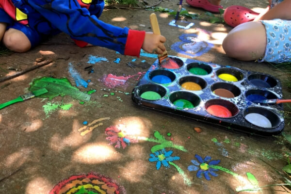 sidewalk chalk paint in a muffin tin with kids painting on the sidewalk with brushes