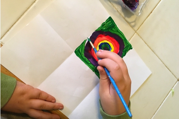 Paper divided into 6 squares. Rainbow colored concentric circles being painted