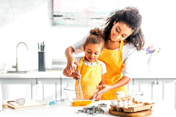 calm mom cooking in the kitchen with a young girl