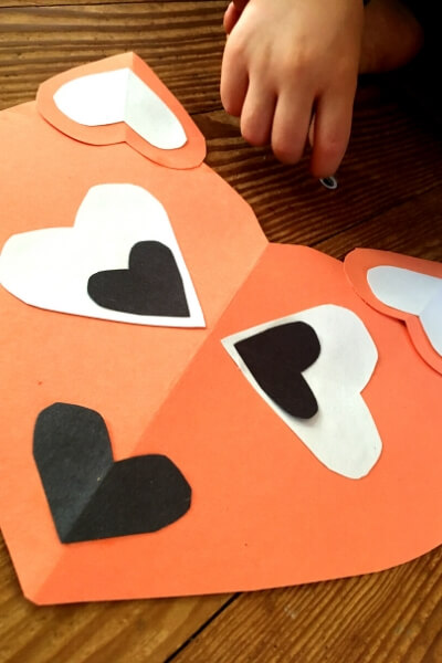 orange paper heart with small white and black hearts for eyes, nose, and ears