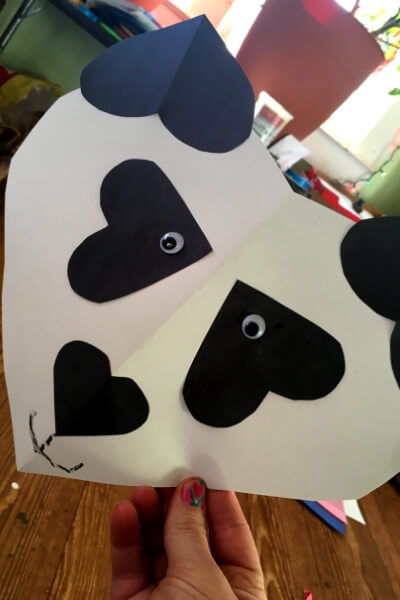 large white paper heart with black paper hearts glued together to looking like a panda