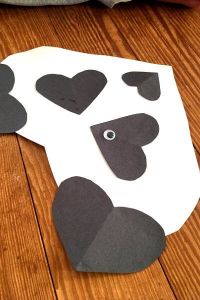 large white paper heart with black paper hearts ears, eyes, and nose glued together to looking like a panda