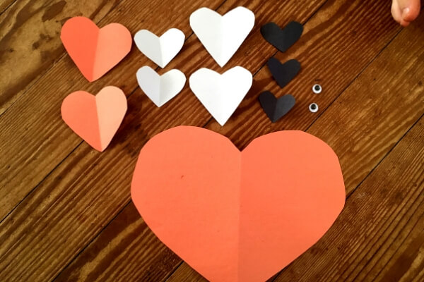 small and large orange, while, and black paper hearts