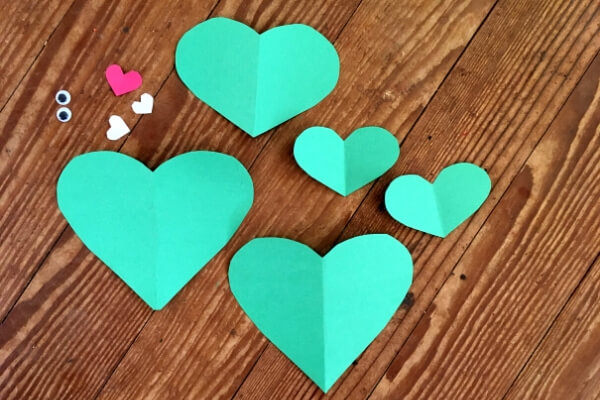 5 green paper hearts, 2 tiny white paper hearts, a tiny red paper heart, and 2 googly eyes