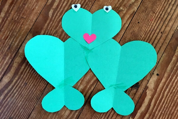 green frog made out of 5 green paper hearts glued together with white heart eyes and a red heart mouth and 2 googly eyes