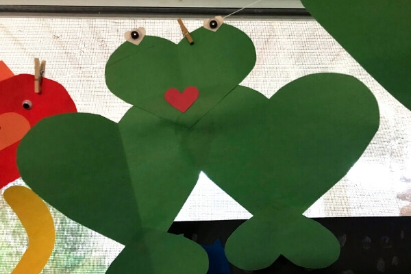 green frog made out of 5 green paper hearts glued together with white heart eyes and a red heart mouth