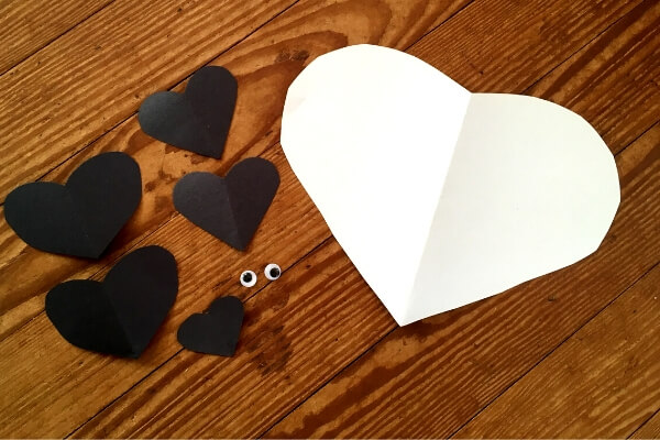 one large white heart and 5 small black paper heart and 2 googly eyes