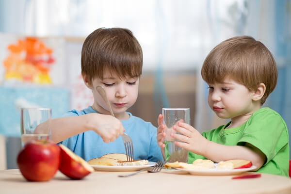 2 boys at a table eating lunch