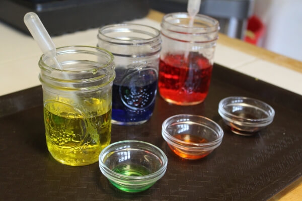 jars of colored water and pipettes for mixing colors
