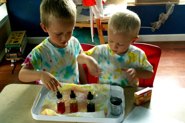 2 boys at a table mixing colored water