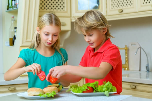siblings making their own sandwiches for lunch