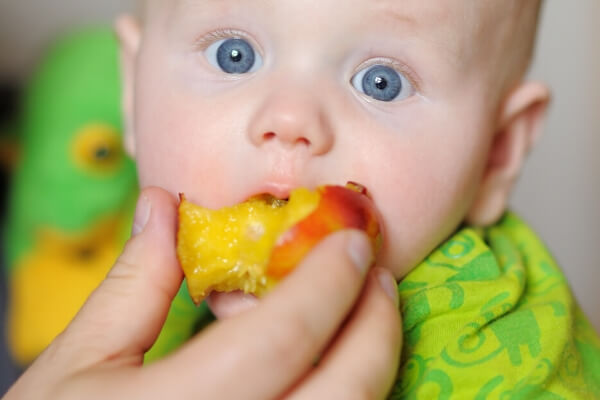 small baby being fed a peach