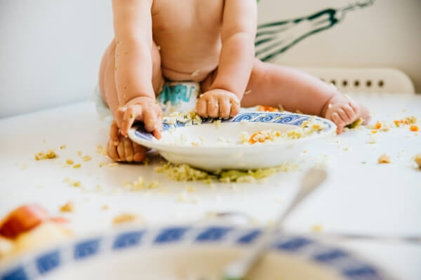 baby making a mess feeding himself while sitting in table