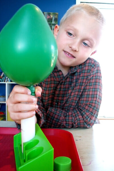 boy blowing up a balloon with a test tube filled with baking soda and vinegar