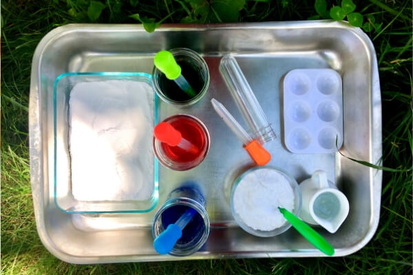 Roasting pan filled with containers and bowls of baking soda and jars of colored vinegar with droppers for a sensory bin for kids