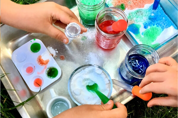 kids hands playing with baking soda and vinegar and various droppers, spoons, and bowls