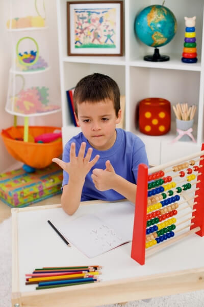 young boy doing math on hands