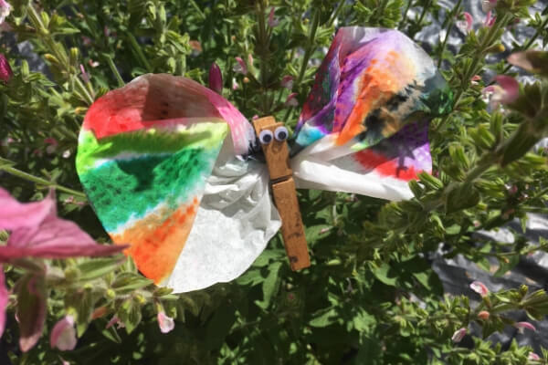 coffee filter and clothes pin butterfly sitting in a pink sage flower plant
