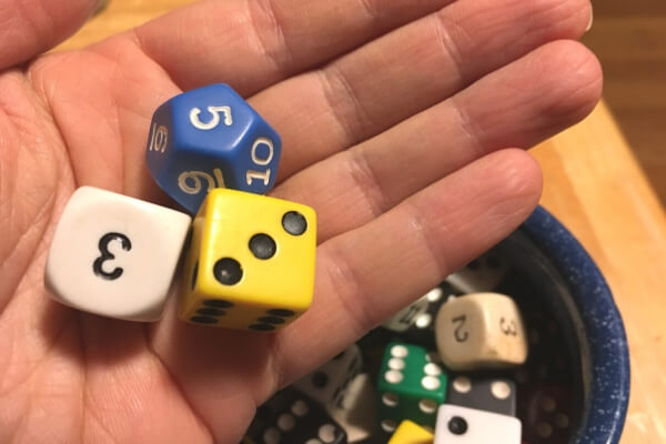 hand holding 3 types of dice- standard, 12 sided, and one with numbers instead of dots