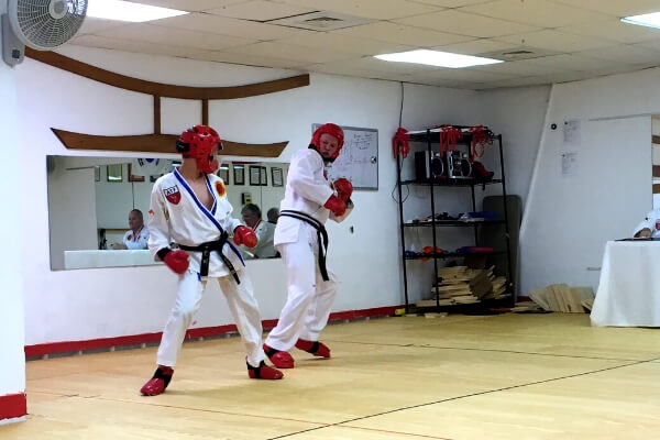 father and son practice martial arts sparring together