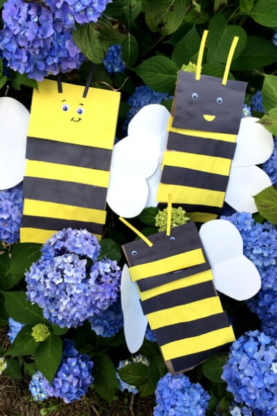 2 finished paper bag bee puppets in a flower bush with purple flowers