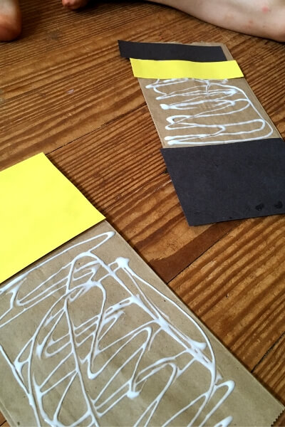 paper bags with yellow and black paper being glued on
