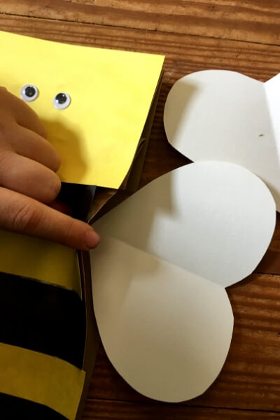 gluing white heart shaped wings on a paper bag bee puppet