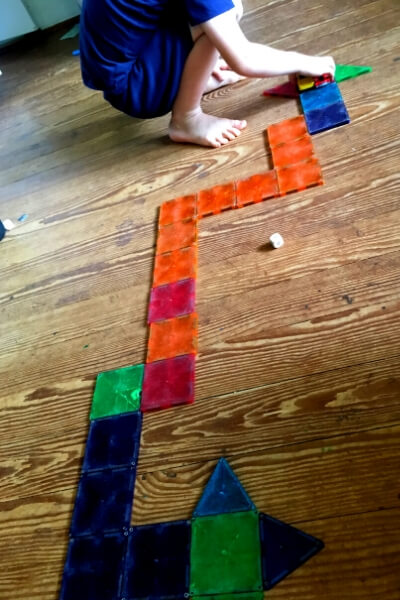 race track made out of magna tiles for a racing math game