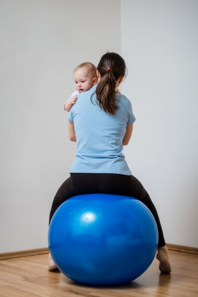 Mother calming a baby by bouncing on an exercise ball