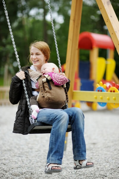 mother swinging on swings with a baby in a carrier