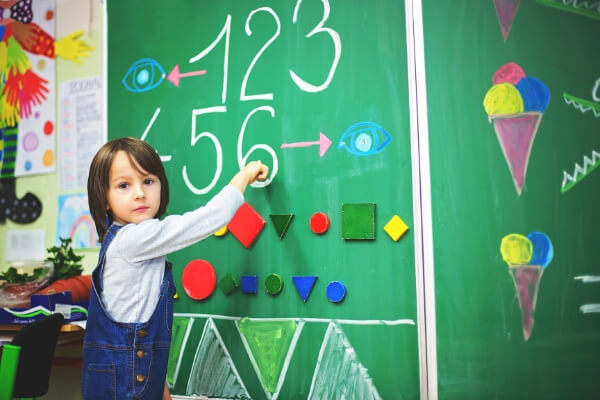 small boy finding numbers and pointing to the number 6