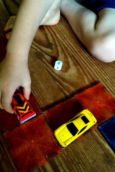 small hands moving a car along a race track with a dice to show how many spaces to move