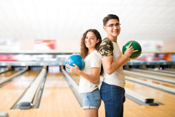 a teenage boy and girls standing back to back in a bowling alley holding bowling balls