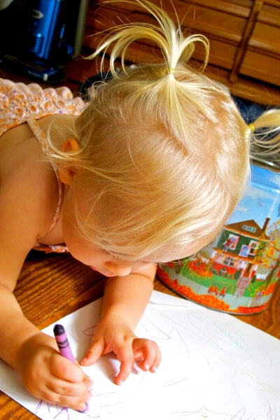 toddler coloring on a piece of paper with a crayon