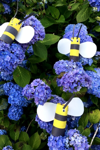 3 toilet paper roll bees in a hydrangea bush with purple flowers