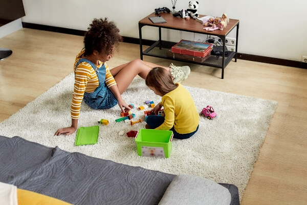 teenage babysitter sitting on floor playing with young girl