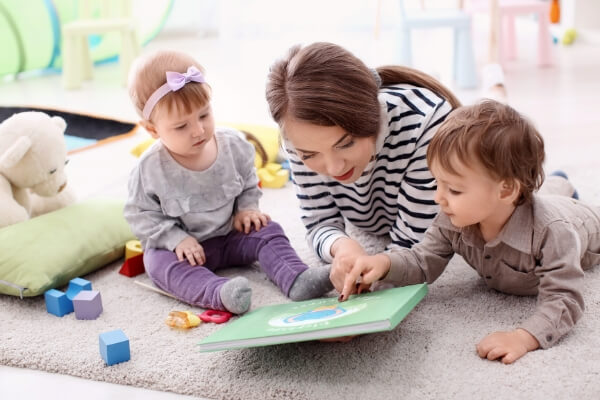 young babysitter reading on the floor with 2 young children