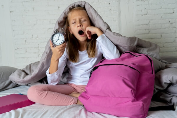 young girl yawning in bed on a school morning with a backback and alarm clock
