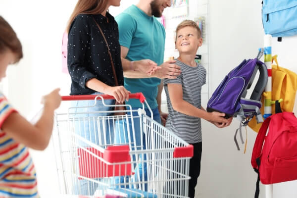 boy and family back to school shopping for backpacks