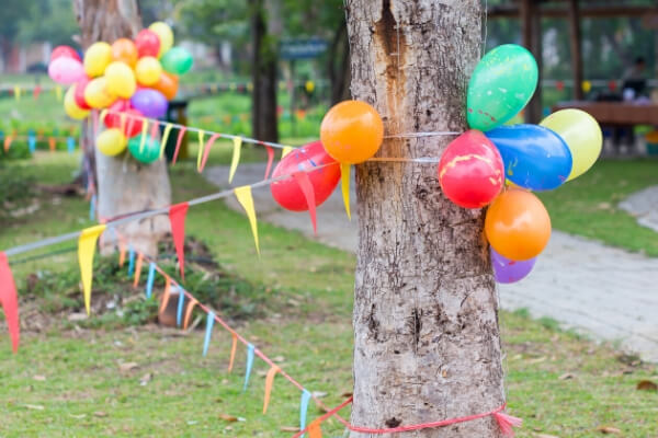 balloons and streamers decorating a backyard for a birthday party