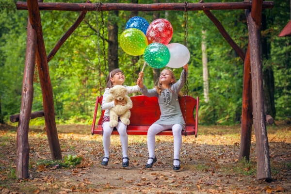 2 girls of backyard swing with birthday balloons