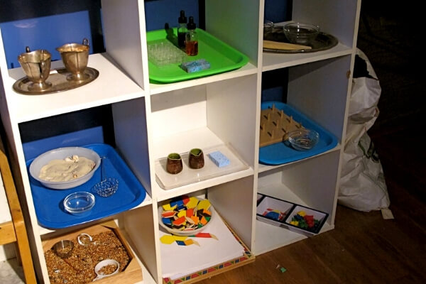 shelf of montessori inspired materials for preschool