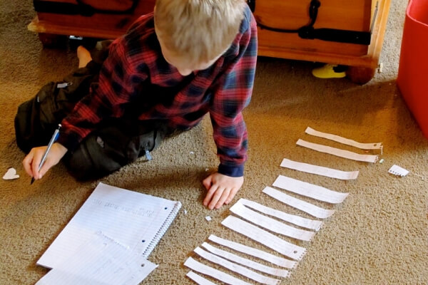 boy writing notes on slips of paper for a research paper