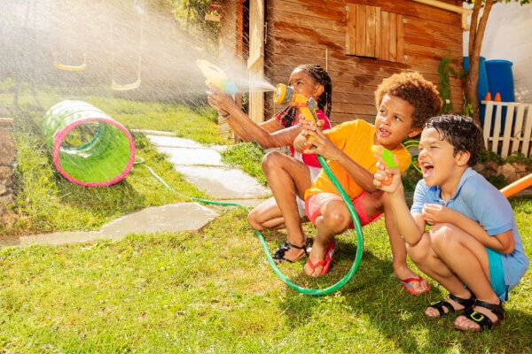 kids spraying each other with hoses at a water party