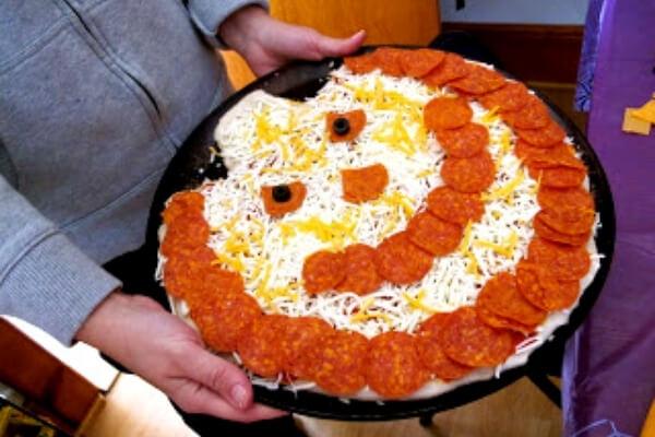 homemade pizza shaped like a jack-o-lantern for halloween