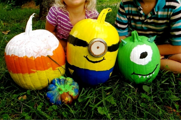 pumpkins painted as candy corn, a monster, and a minion for Halloween