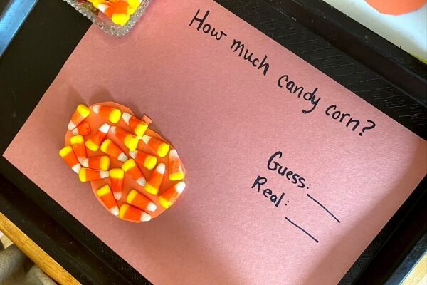guessing game estimating number of candy corn that can fit inside a paper pumpkin
