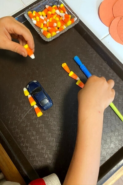 child measuring a car and paint brush with candy corn